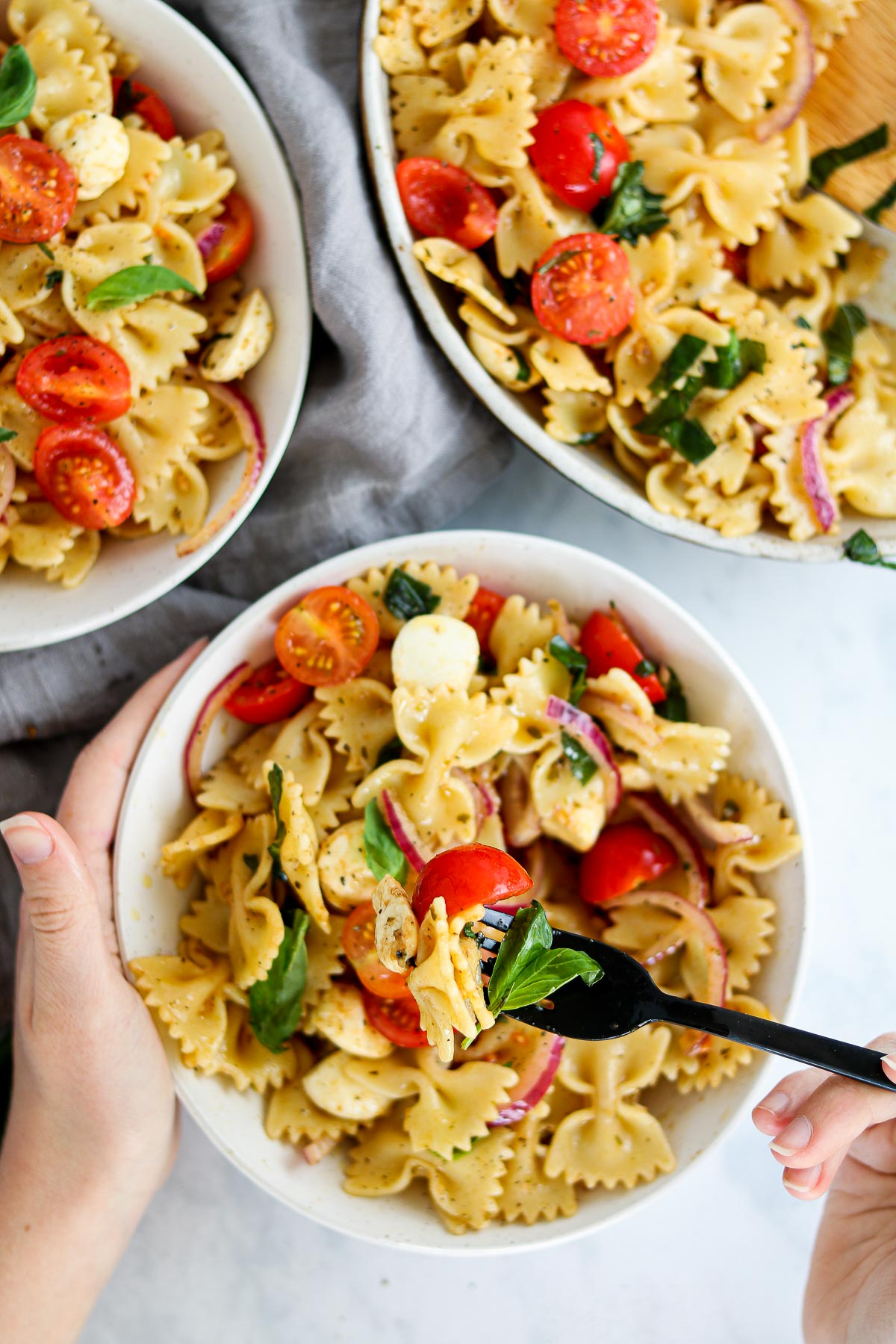 Pasta with cherry tomatoes, mozzarella, basil, and a balsamic dressing in a bowl