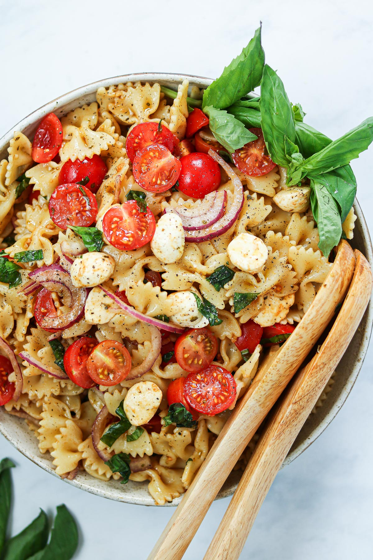 Pasta with cherry tomatoes, mozzarella, basil, and a balsamic dressing in a serving bowl