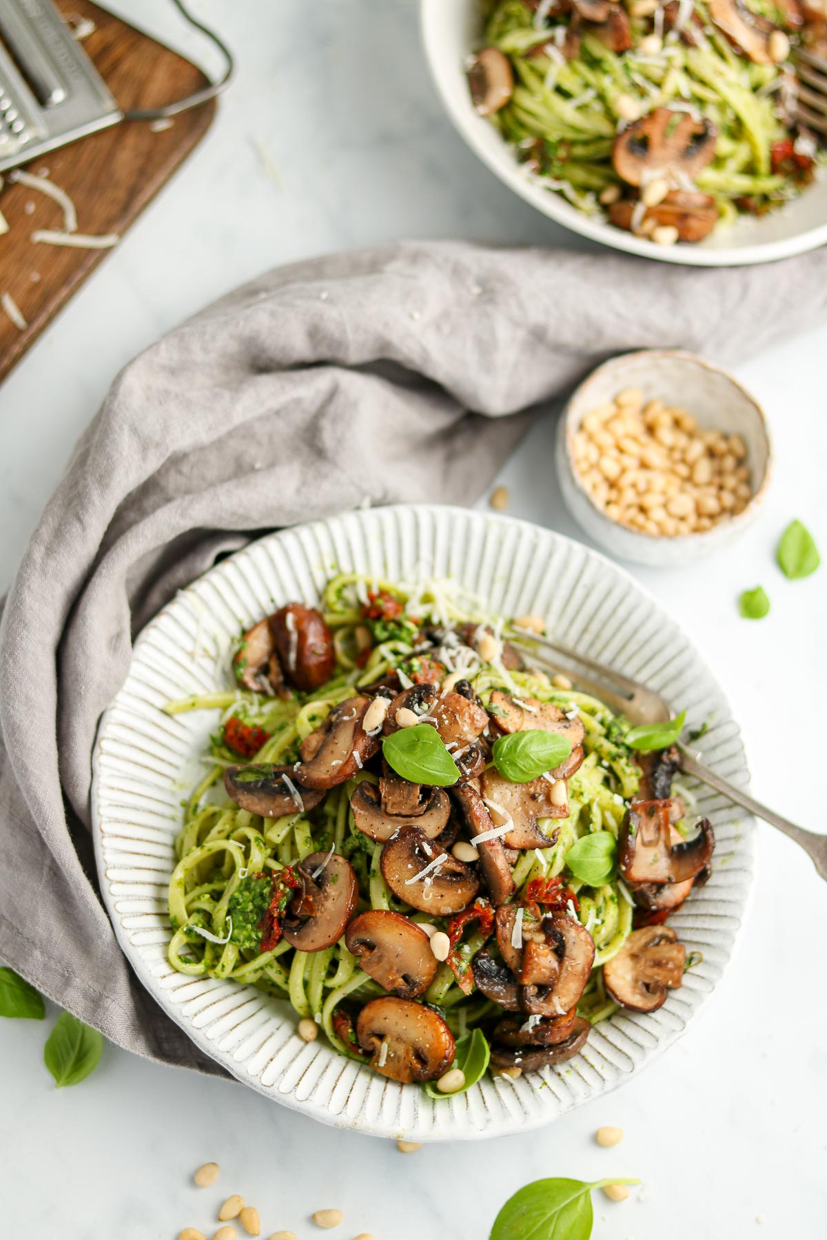 Pasta covered in pesto sauce with mushrooms