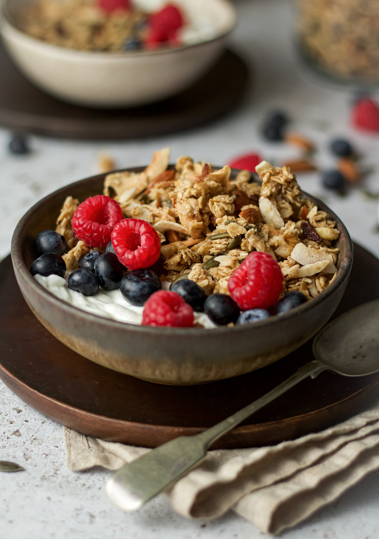 side on view of granola in bowl with berries and yoghurt