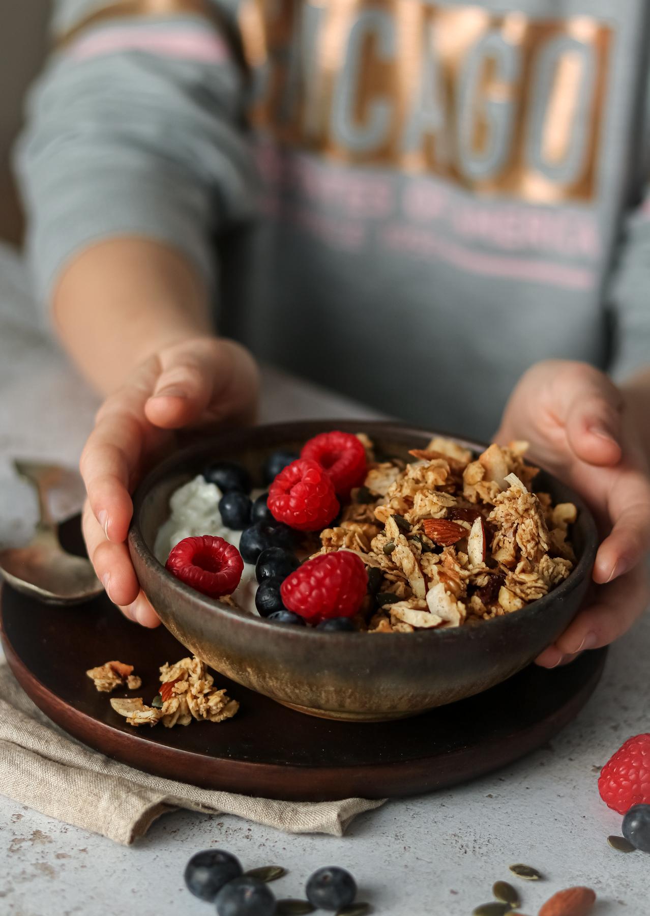 child picking up bowl of granola