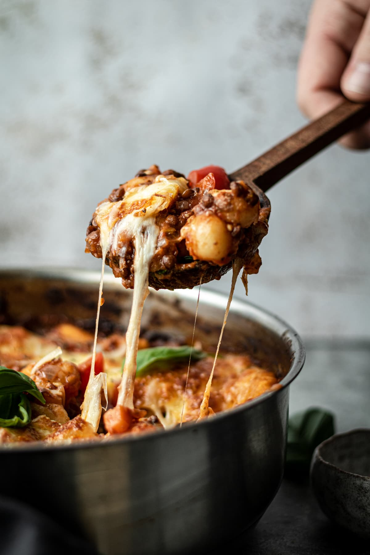 A spoonful of gnocchi bolognese being lifted from pan with cheese