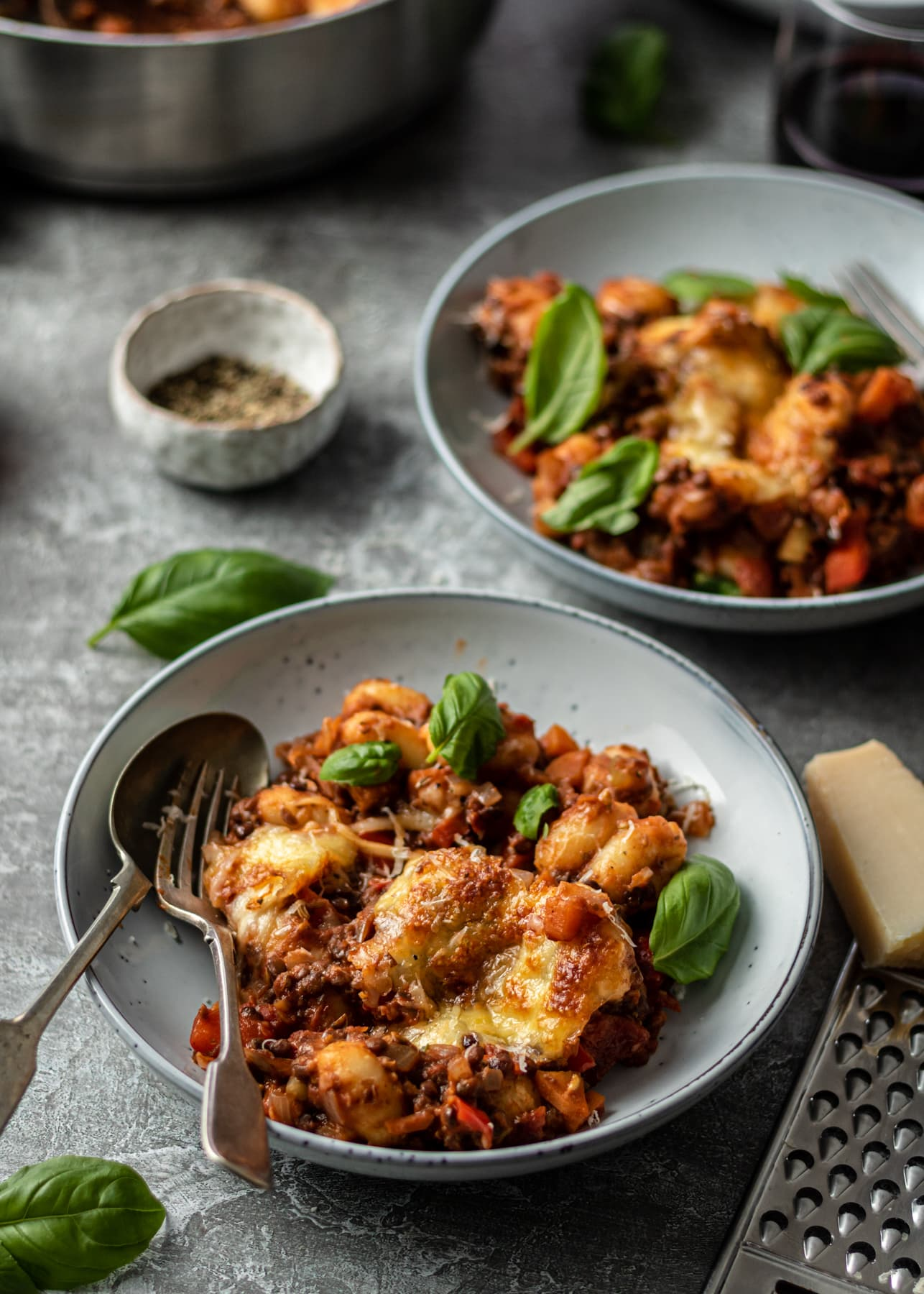 Gnocchi bolognese in bowls with spoons and forks