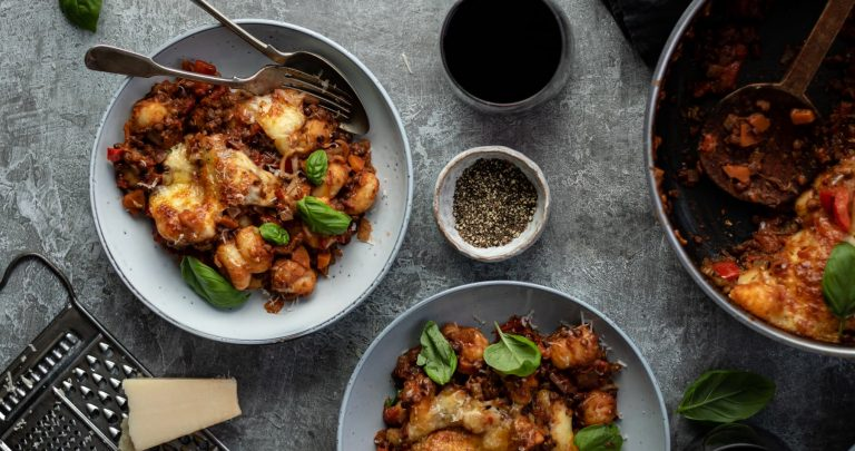 landscape image of overhead view of gnocchi bolognese