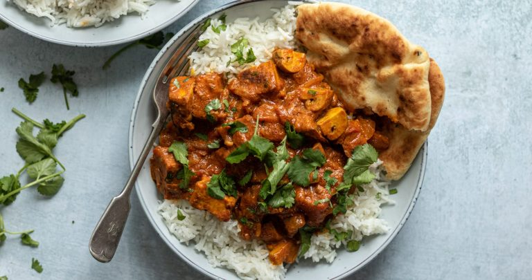 overhead image of tofu tikka masala in bowl with naan and rice