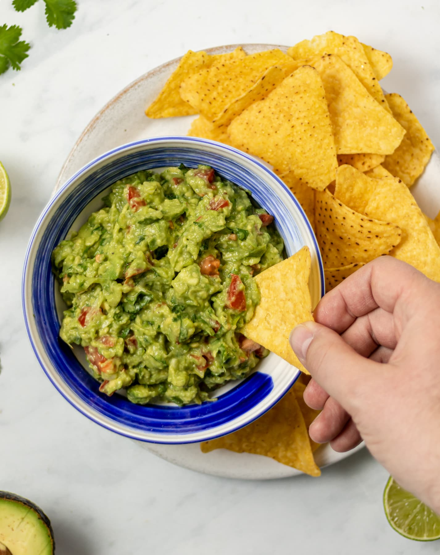 guacamole in a bowl on a plate surrounded with tortilla chips. Hand reaching into bowl with tortilla chip.