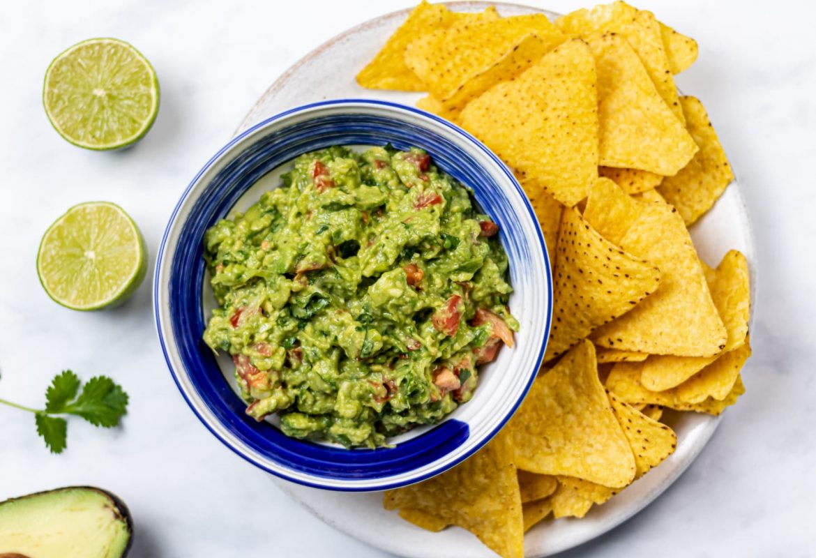 landscape overhead image of guacamole in a bowl, on a plate with tortilla chips. Cut limes to the side.