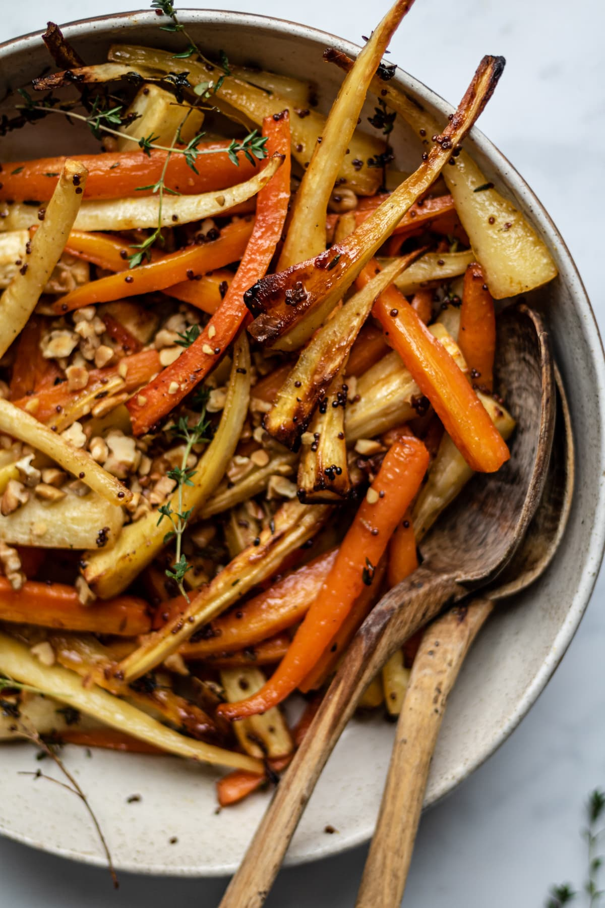Close up image of roasted carrots and parsnips in a serving dish with serving spoons