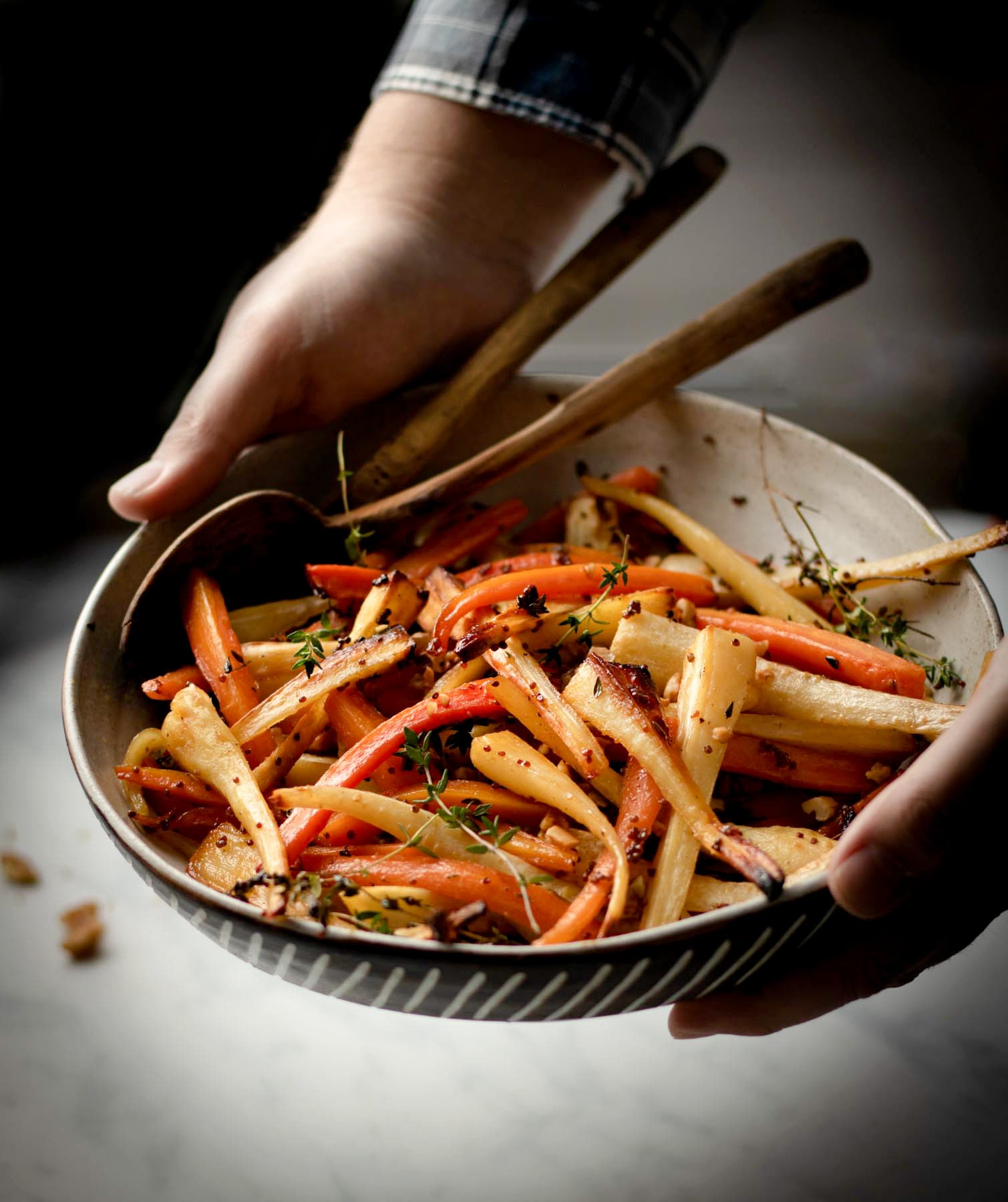 Hands holding serving bowl filled with roasted carrots and parsnips