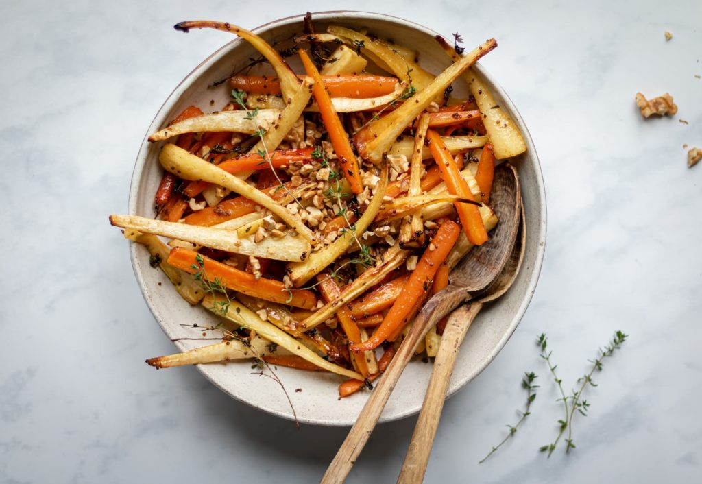 Landscape overhead image of roasted carrots and parsnips in serving bowl