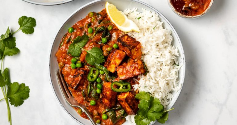 Paneer cheese in curry sauce with peas, spinach, rice and a coriander garnish