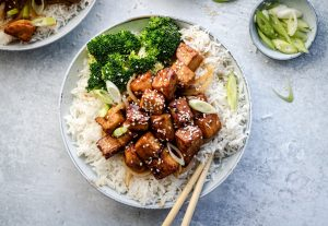 Glazed tofu with sesame seeds, onion garnish, white rice and broccoli