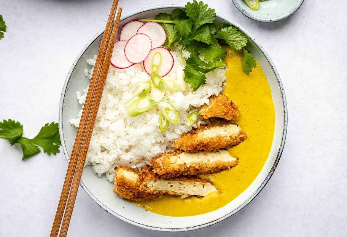 Deep fried tofu in breadcrumb served with rice and a curry sauce