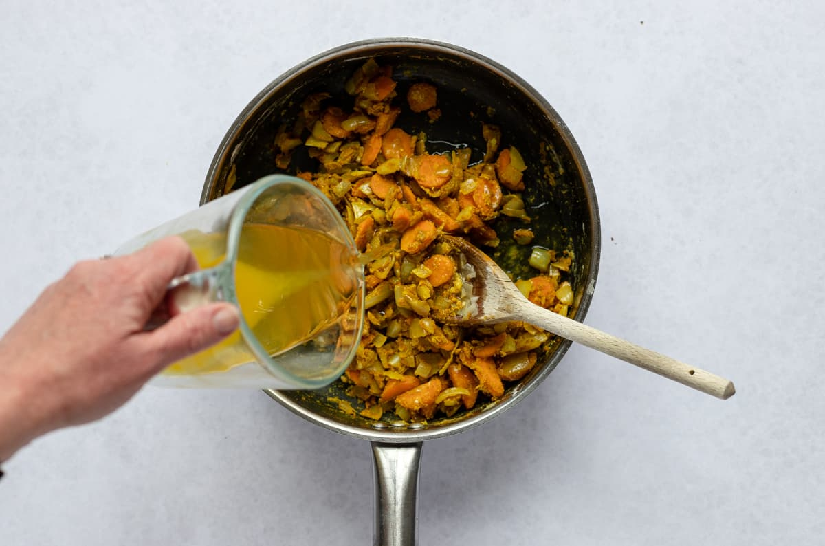 Pouring stock on fried onion and carrots in pan
