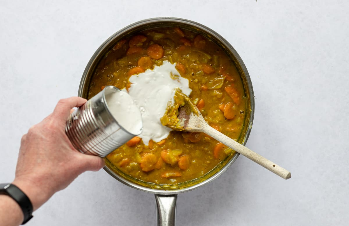 Pouring coconut milk into curry in pan