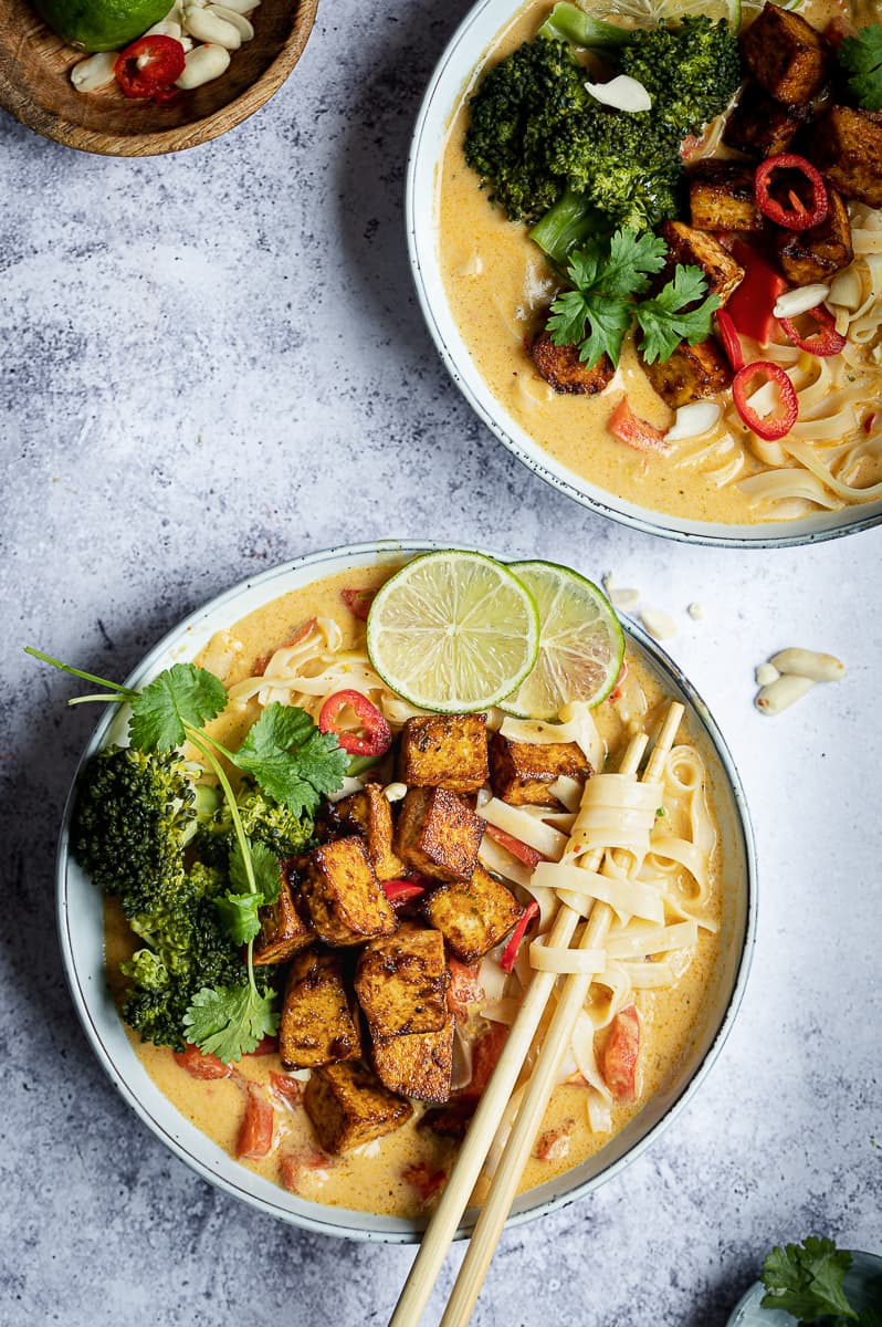 Pasta in a creamy Thai spiced sauce with crispy tofu, broccoli, and lime wedges