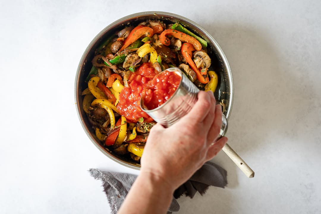 Vegetables with tin tomatoes in pan