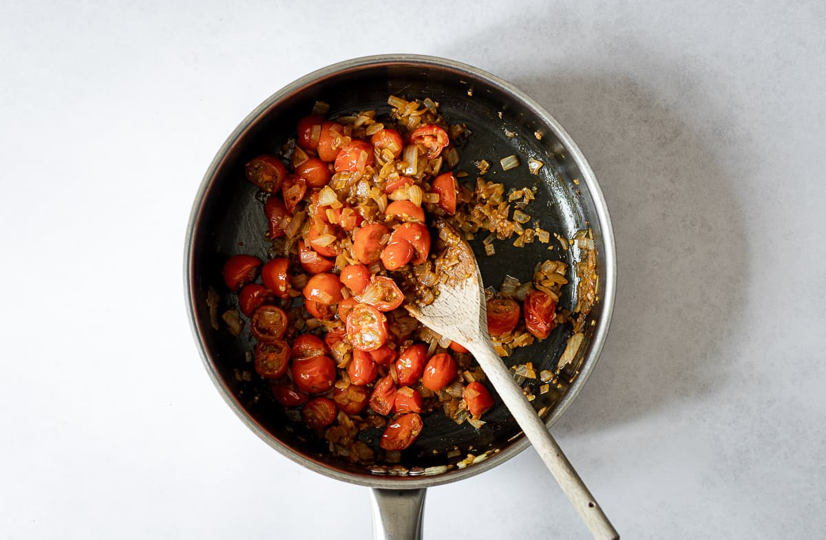 tomatoes and onions cooking in pan