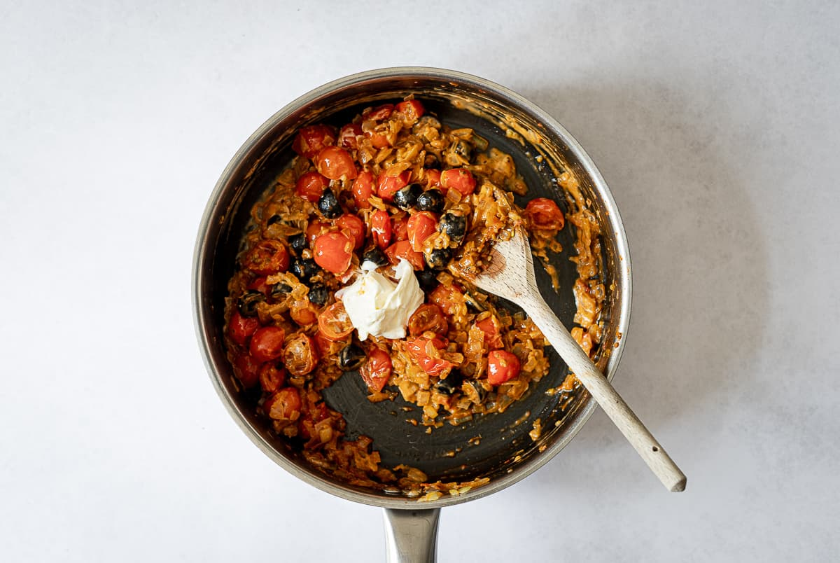 tomatoes, onions and olives cooking in pan