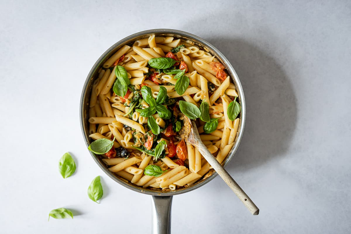 pasta with basil garnish cooking in pan with sauce