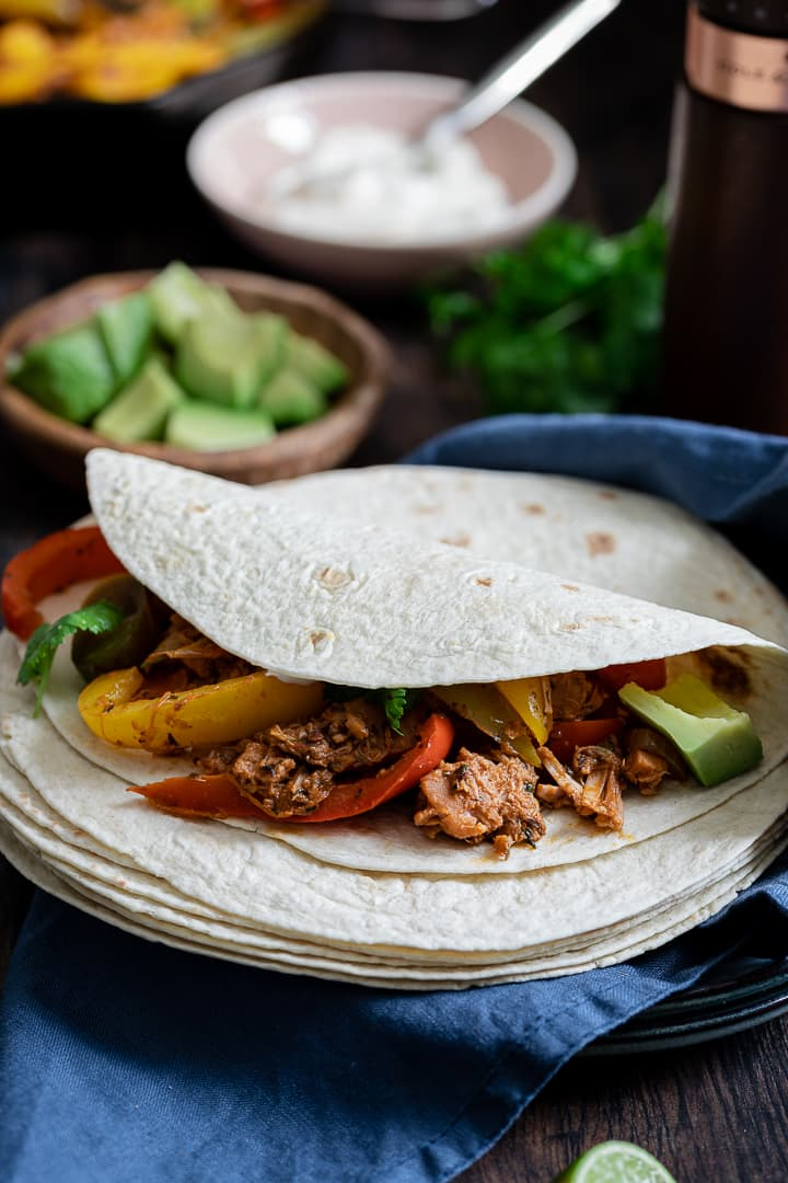 Jackfruit with peppers and a coriander garnish wrapped in a tortilla