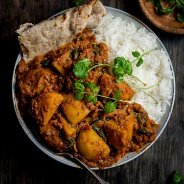 Potatoes in a curry sauce with lentils, rice and naan, with coriander garnish