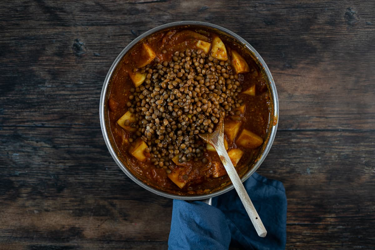 Lentils being added to a pan with potatoes and sauce